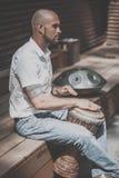 供以人员演奏坐在公园的鼓djembe 免版税图库摄影