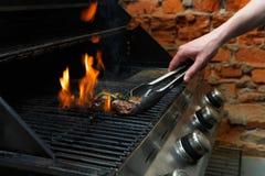 供以人员烹调在专业格栅的肉牛排户外 免版税库存图片