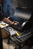 供以人员烹调在烤肉的使有大理石花纹的肉汉堡的 免版税库存照片