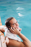 供以人员用途在水池的边缘的手机 免版税图库摄影