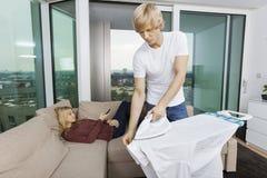 供以人员电烙的衬衣,当在家时放松在沙发的妇女 免版税库存照片