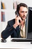 供以人员看一台计算机显示器,在电话 免版税图库摄影
