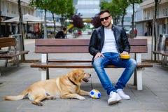 供以人员看与他的说谎在他旁边的狗的照相机 免版税库存图片