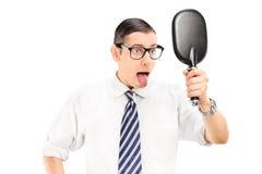供以人员看在镜子和伸出他的舌头  库存照片