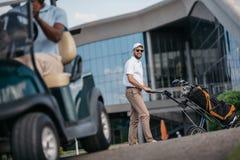 供以人员看照相机,当滚动与高尔夫俱乐部的高尔夫球袋在它时 免版税库存图片
