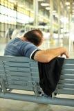 供以人员睡觉在火车站的一条长凳 免版税库存照片