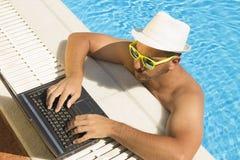 供以人员研究膝上型计算机在游泳池边缘 下来上面观点 免版税库存图片