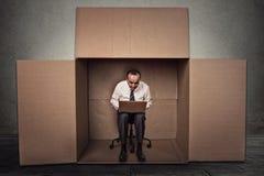 供以人员研究膝上型计算机坐在纸盒箱子里面的椅子 免版税库存图片