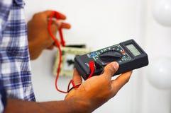供以人员穿运转在电子壁上插座导线的白色和蓝色衬衣使用多用电表,电工概念 免版税库存图片