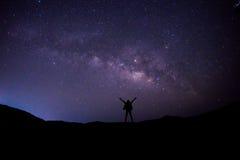 供以人员立场在与星和银河的夜空视图 库存图片