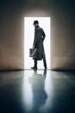 供以人员站立根据在黑暗的roo的开门的剪影 免版税库存图片