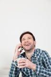 供以人员笑在有一杯咖啡的手机 免版税库存照片