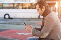 供以人员等待在汽车站和看他的智能手机 库存图片