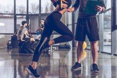 供以人员行使用trx健身房设备的帮助的嬉戏妇女 库存照片
