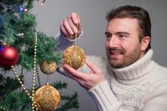 供以人员装饰与金黄球的一棵圣诞树 免版税库存图片