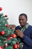 供以人员装饰圣诞树和看照相机 免版税库存照片