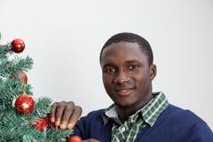 供以人员装饰圣诞树和看照相机 库存照片
