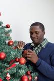 供以人员装饰圣诞树和看照相机 免版税库存图片