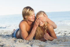 供以人员覆盖物说谎在海滩的女朋友眼睛 库存照片