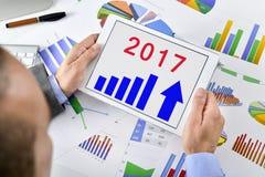 供以人员观察经济展望在2017年在他的片剂 免版税库存图片
