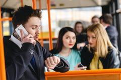 供以人员谈话在手机,公共交通 库存图片