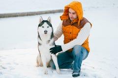 供以人员走与狗与雪的冬时在森林爱斯基摩友谊 图库摄影