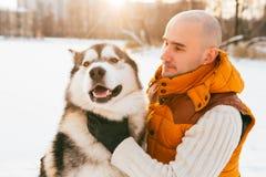 供以人员走与狗与雪的冬时在森林爱斯基摩狗友谊 免版税库存图片