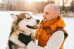 供以人员走与狗与雪的冬时在森林爱斯基摩狗友谊 免版税库存照片