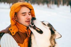 供以人员走与狗与雪的冬时在森林爱斯基摩狗和爱斯基摩友谊 库存照片