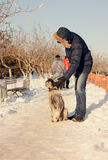 供以人员走出去与他的在雪的狗 免版税库存照片
