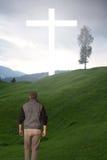 供以人员走到在一个绿色领域的十字架 库存照片