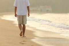 供以人员走和留下脚印在海滩的沙子 免版税库存照片