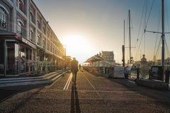 供以人员走在有日落的江边港口开普敦 库存照片