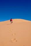 供以人员走在沙丘到天空 库存图片