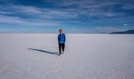 供以人员走在湖撒拉族de Uyuni,玻利维亚 库存图片
