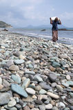 供以人员走在蓝色小卵石在Pengajawa海滩弗洛勒斯印度尼西亚 免版税库存图片