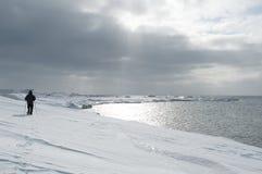供以人员走在雪的雪靴在海边 图库摄影