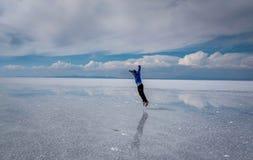 供以人员跳跃在湖撒拉族de Uyuni,玻利维亚 免版税库存图片