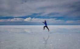 供以人员跳跃在湖撒拉族de Uyuni,玻利维亚 库存图片