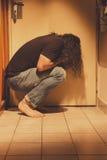 供以人员蹲下在地垫,哀伤,沮丧和孤独 免版税图库摄影