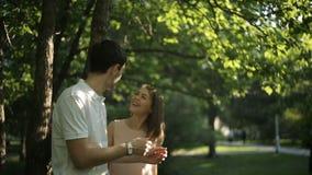 供以人员身分在树下,她拾起从他的电话 股票录像
