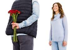 供以人员躲藏起来从在他的后的一朵玫瑰他的妇女 库存照片