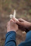 供以人员运转衣服的` s手雕刻有刀子的一把木匙子 库存照片