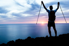 供以人员远足在山、海洋和日落的剪影 免版税库存照片