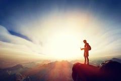 供以人员连接用他的智能手机在山顶部 通信 免版税库存图片