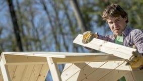 供以人员适合木头的部分对一个室外小屋 库存照片