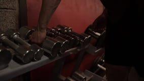 供以人员采取从存贮机架的哑铃在健身房 影视素材