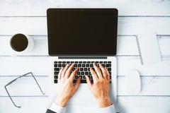 供以人员键入在有一杯咖啡的一台膝上型计算机和辅助部件 库存图片
