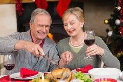 供以人员雕刻鸡,当他的喝红葡萄酒时的妻子 免版税库存照片