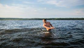 供以人员飞溅水在暑假期间-年轻可爱的男性获得乐趣在河海滩在日落 免版税图库摄影